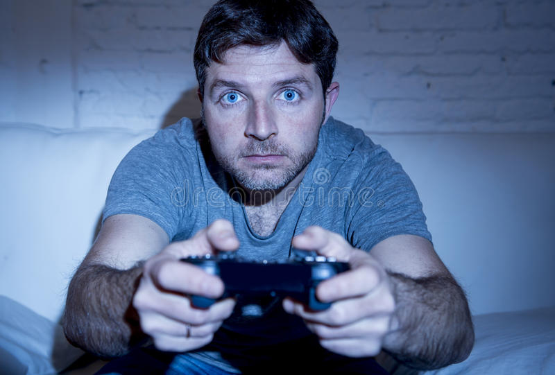 Young excited man at home sitting on living room sofa playing video games using remote control joystick royalty free stock photos