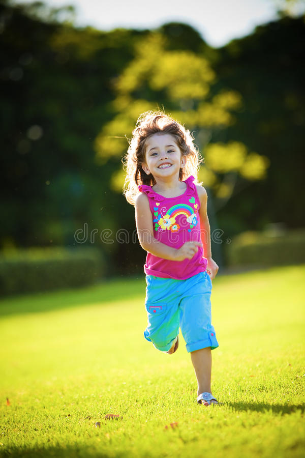 Young excited and smiling girl running. In the sunlit grass royalty free stock image