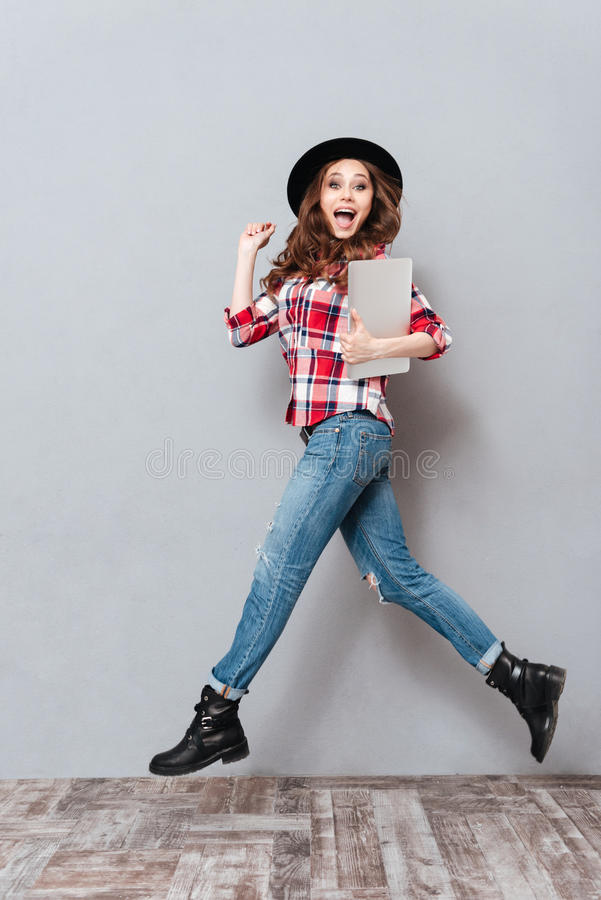 Young excited woman in hat holding laptop and jumping royalty free stock photography