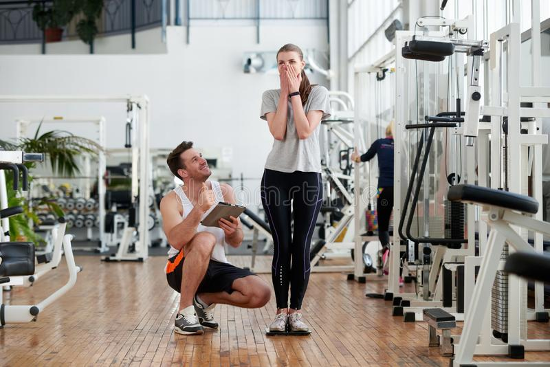 Young excited woman weighing on scale at gym. stock photo