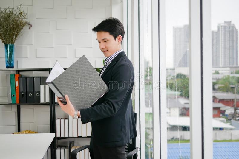Young executive Asian man is standing and holding black file bus royalty free stock image