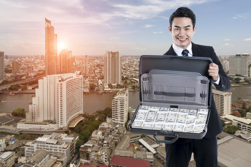 The Young executive man holding a baggage with banknote on cityscape background royalty free stock images