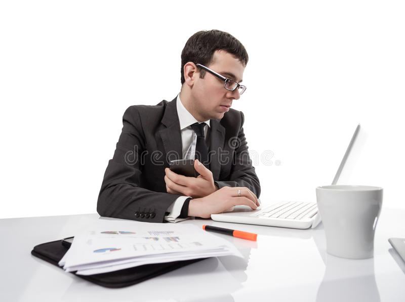 Young executive man working on laptop computer and holding a smartphone royalty free stock photo