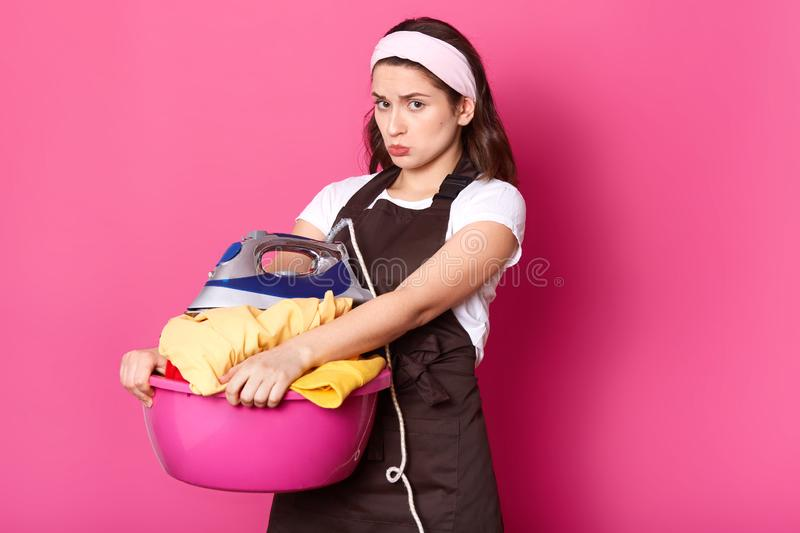 Young exhausted woman, has too much ironing, tired displeased housewife wants to have rest, holds rose basin with fresh linen and. Iron, has unhappy facial royalty free stock images