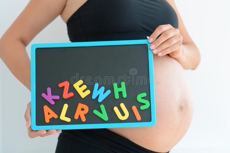 Young expectant mother with magnetic letter blocks trying to choose a name for her baby royalty free stock photography