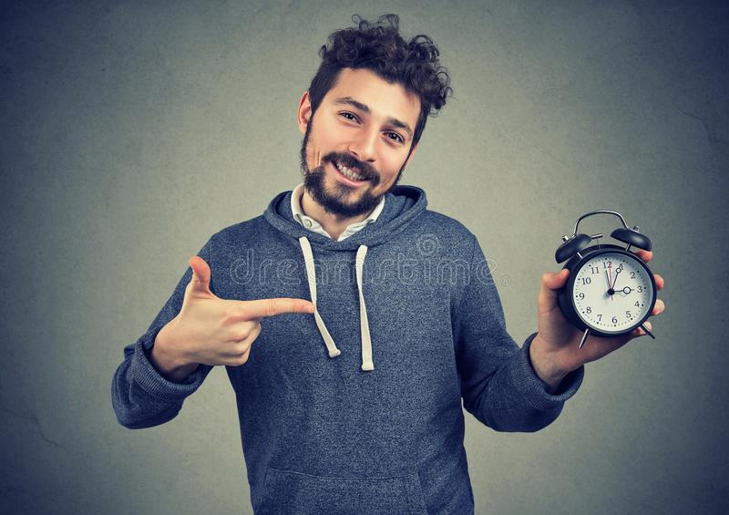 Young expressive happy hipster man holding alarm clock stock photography