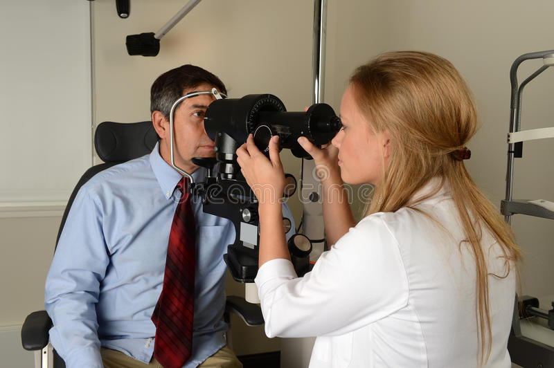 Young Eye Doctor with her patient. During an examination stock photography