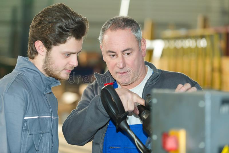 Young factory worker being taught how to use machinery stock photography