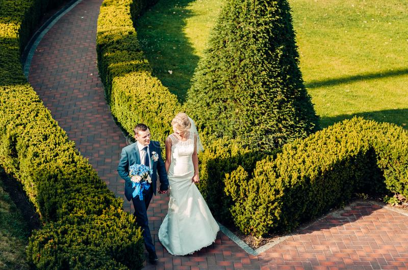 Young fair-haired bride and her fiance walking along stock photos