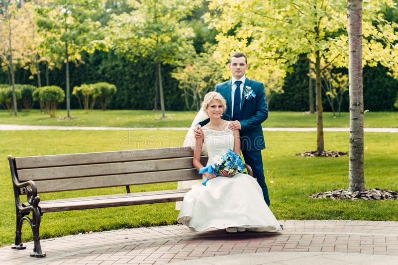 Young fair-haired bride sits on a bench next to the groom in an exotic park royalty free stock images
