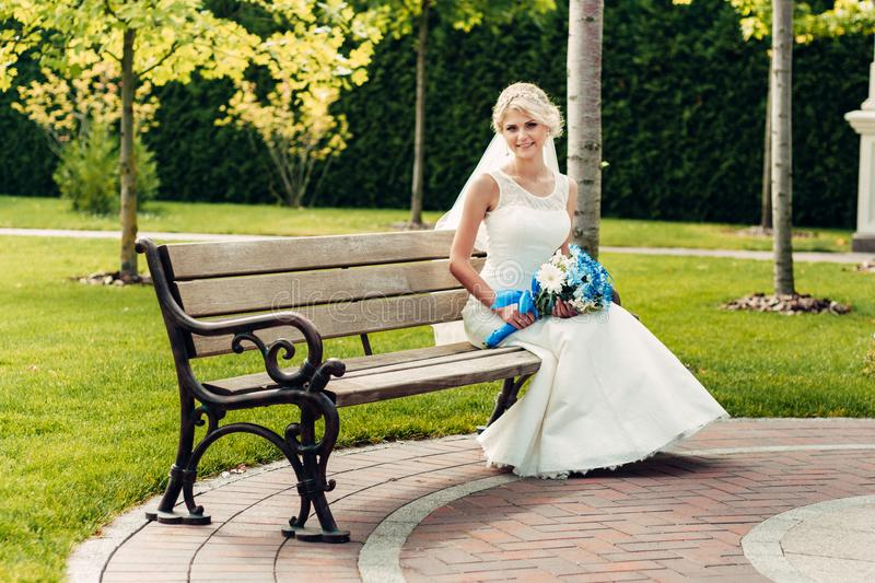 Young fair-haired bride sitting on a bench in an exotic park royalty free stock photography