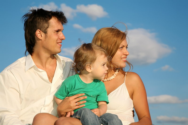 Young family. Looks away against sky stock photos