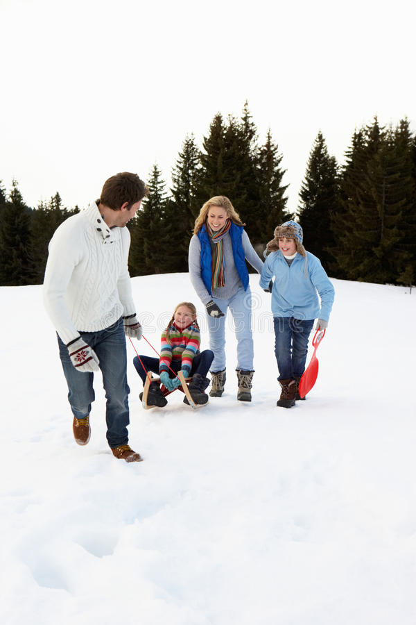 Young Family In Alpine Snow Scene With Sled stock photo
