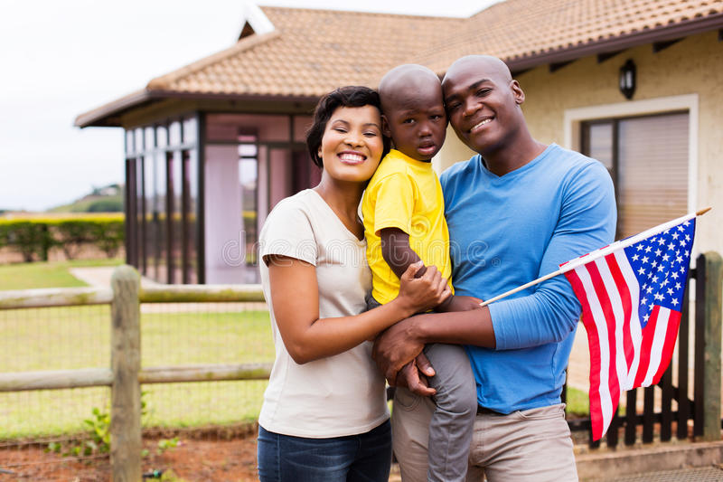 Young family american flag. Portrait of young family holding american flag outside their house stock photos