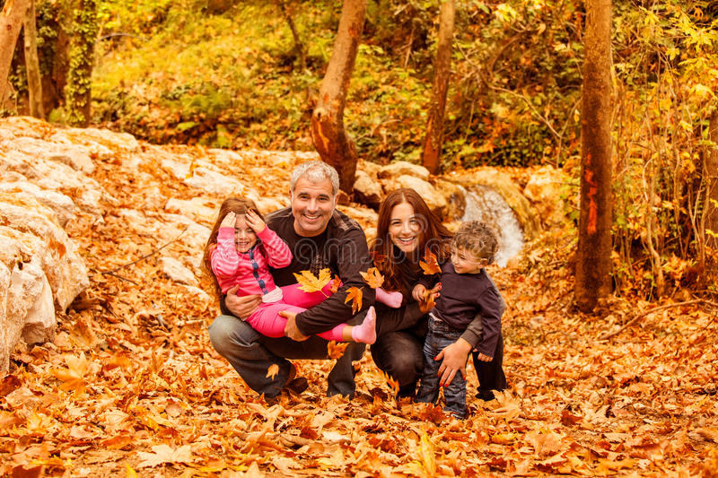 Young family in autumnal forest. Image of beautiful female and men with cute daughter and pretty son having fun in autumnal forest, young parents with nice royalty free stock images