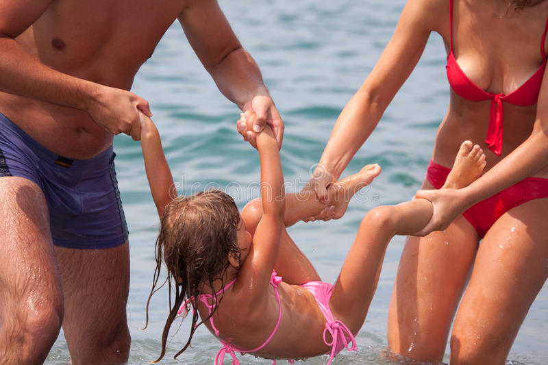Young family bathes in sea. Wet happy daddy and mum play with daughter standing in water stock image
