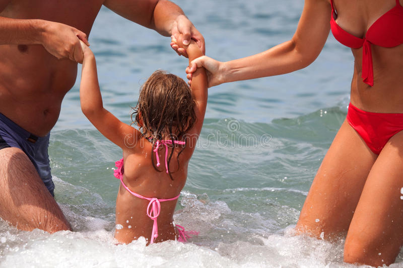 Young family bathes in sea. Wet happy daddy and mum play with daughter standing in water. Parents hold child for hands royalty free stock photos