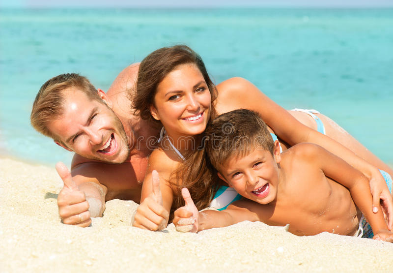 Young Family at the Beach. Happy Young Family with Little Kid Having Fun at the Beach