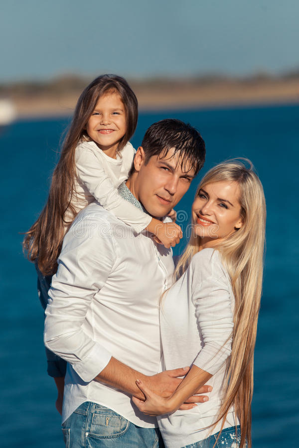 Young family in blue jeans hugging on the royalty free stock photos