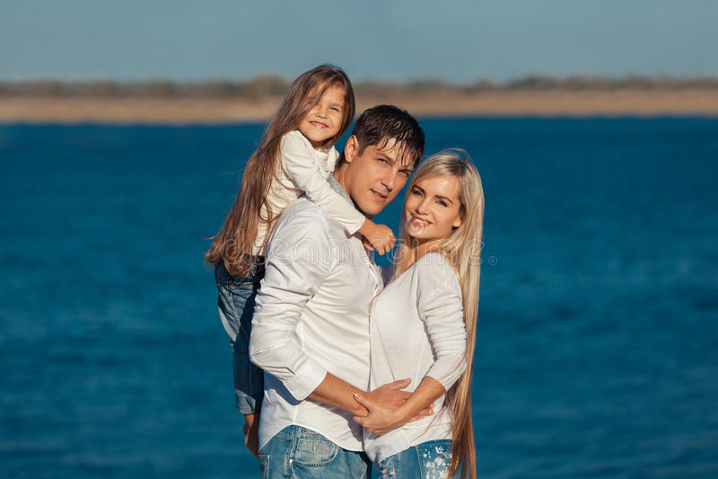 Young family in blue jeans hugging on the royalty free stock image