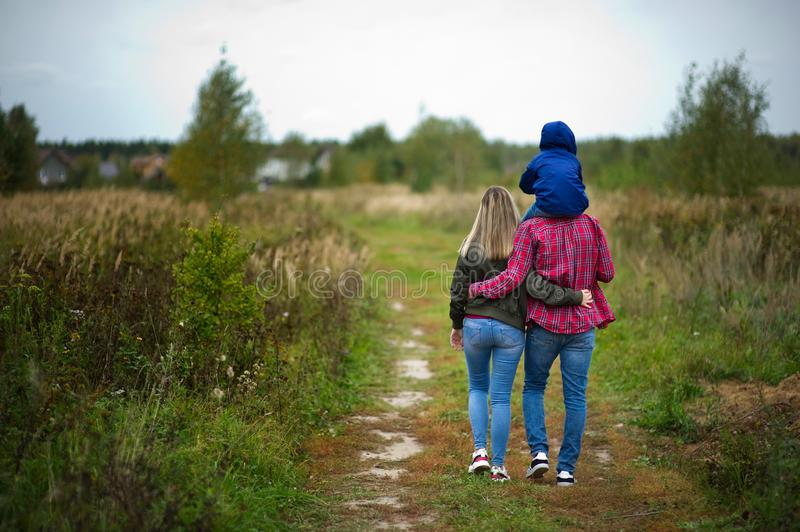 A young family in bright casual clothes walks away along a country road in the field. Little son on father`s shoulders royalty free stock image