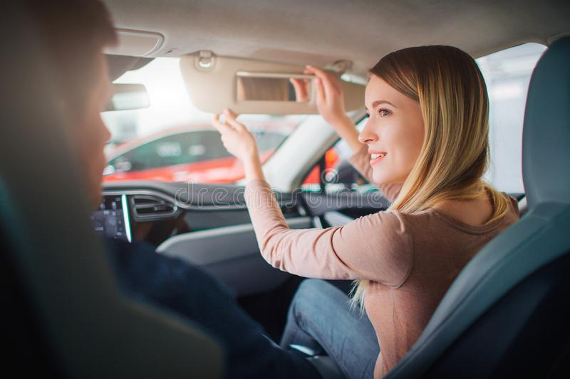 Young family buying first electric car in the showroom. Attractive smiling couple talking in the cabin of modern royalty free stock photo