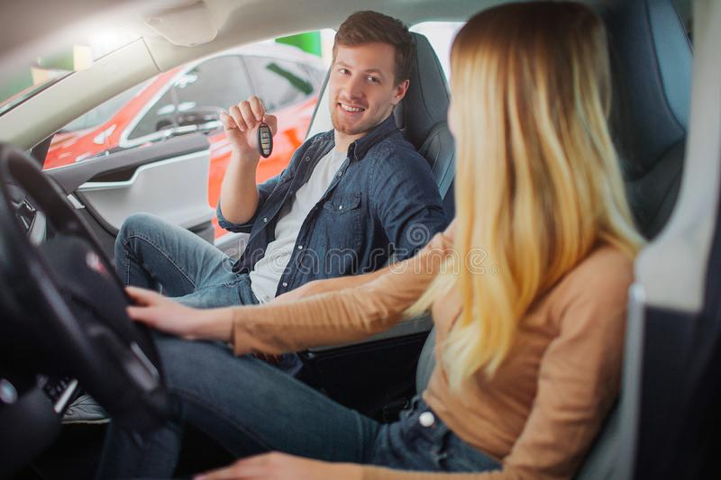 Young family buying first electric car in the showroom. Attractive smiling couple talking and sitting in the cabin of royalty free stock photos