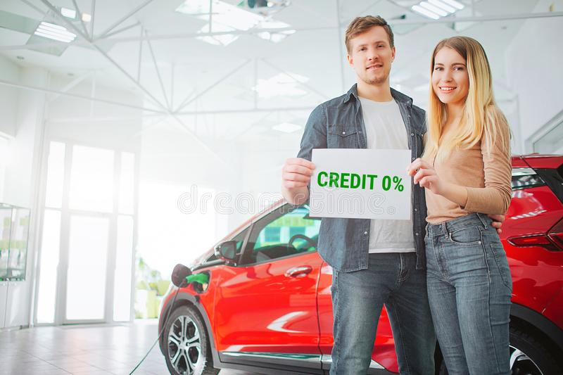 Young family buying first electric car in the showroom. Smiling attractive couple holding paper with word Credit while stock image