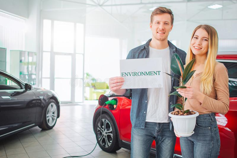Young family buying first electric car in the showroom. Smiling attractive couple holding paper with word Environment royalty free stock photography
