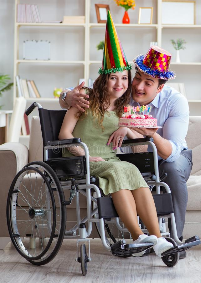 Young family celebrating birthday with disabled person. The young family celebrating birthday with disabled person royalty free stock photos