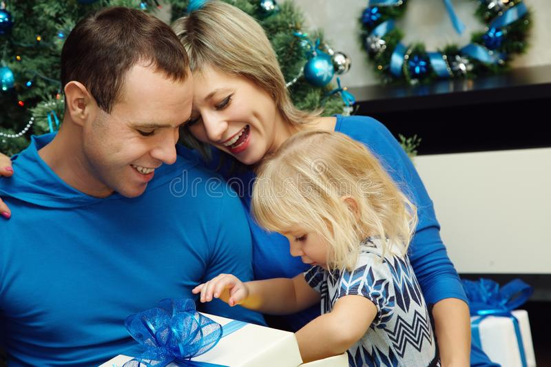 Young family celebrating Christmas at home. father and mother give a child present. New Year and xmas people. stock photo