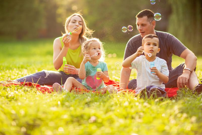 Family with children blow soap bubbles outdoor. Young family with children blow soap bubbles outdoor stock photos