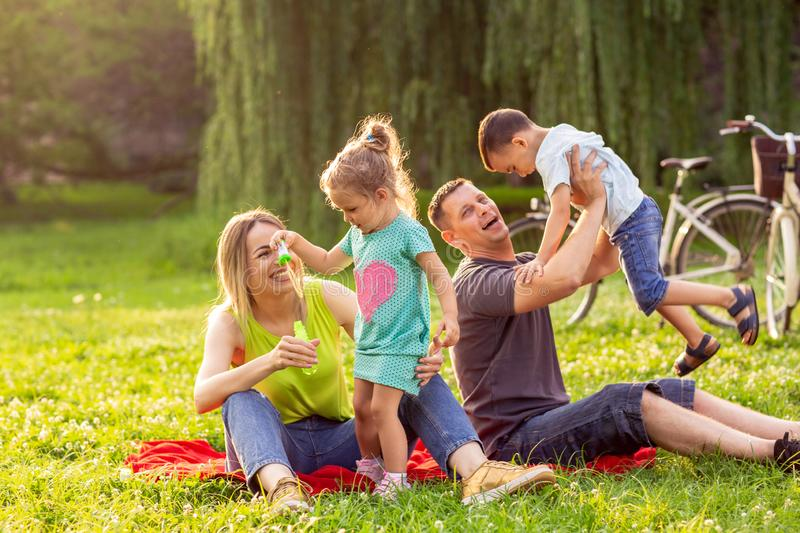 Young family with children having fun in nature stock photography