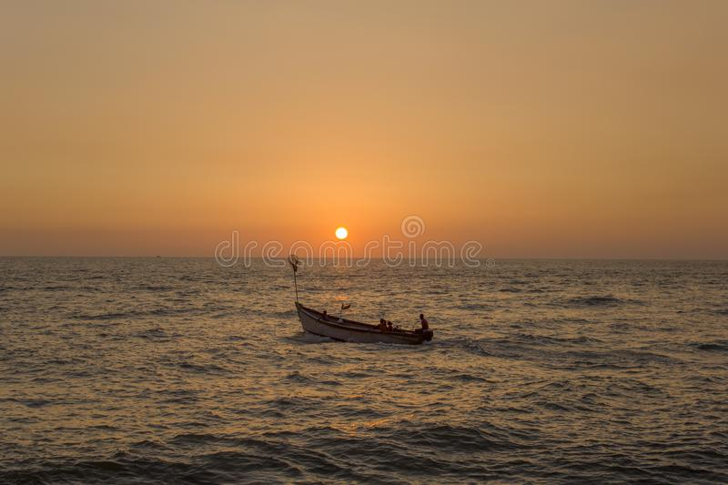 Young family with children in a large pleasure boat with a motor in the ocean against the bright orange yellow sky of sunset and stock image