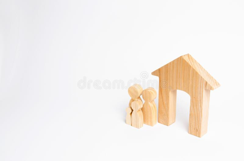 A young family with children is standing near a wooden house. The concept of a strong family, the continuation of the family. Loans for the purchase of stock photography