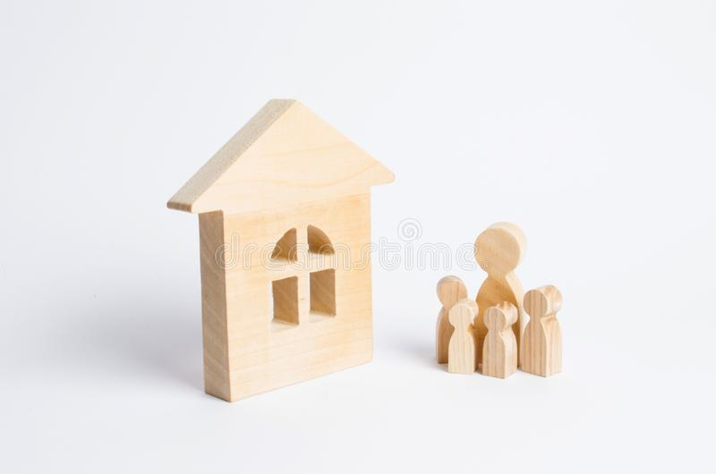 A young family with children is standing near a wooden house. The concept of a strong family, the continuation of the family. Loans for the purchase of stock image