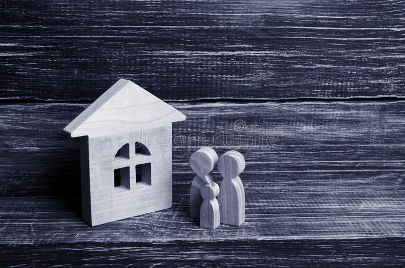 A young family with children is standing near a wooden house. The concept of a strong family, the continuation of the family. Loans for the purchase of stock photos