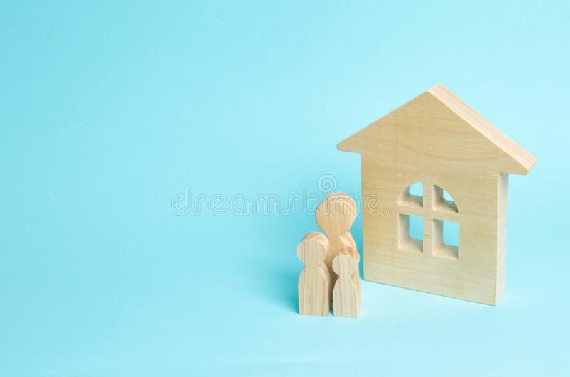 A young family with children is standing near a wooden house. The concept of a strong family, the continuation of the family. Loan. S for the purchase of royalty free stock image