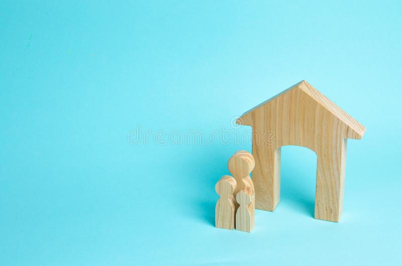 A young family with children is standing near a wooden house. The concept of a strong family, the continuation of the family. Loans for the purchase of royalty free stock photography