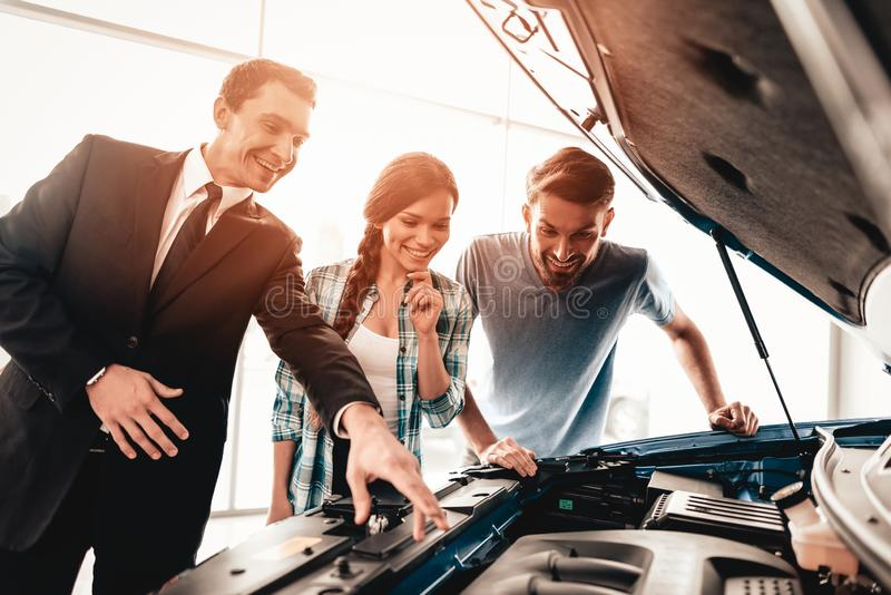 Young Family Are Choosing A New Car In Showroom. Happy Young Family Are Choosing A New Car In Showroom. Dialogue With Dealer. Cheerful Customer. Automobile stock photography