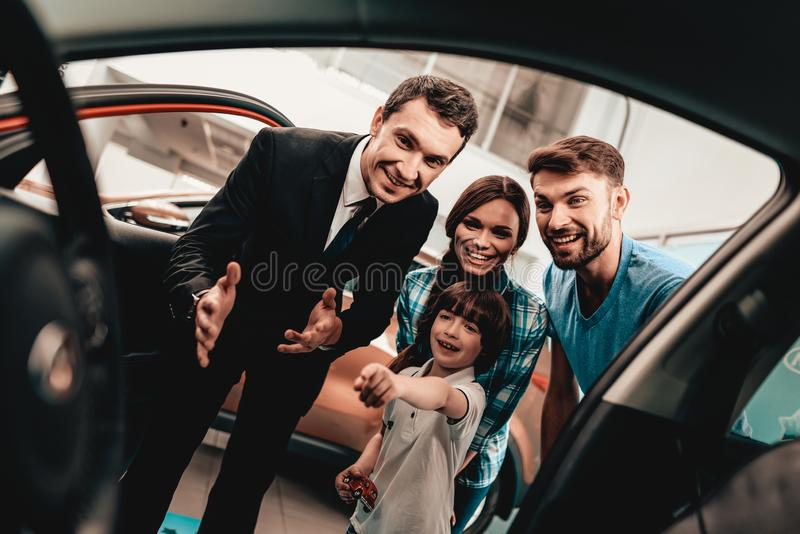 Young Family Are Choosing A New Car In Showroom. Happy Young Family Are Choosing A New Auto In Showroom. Dialogue With Dealer. Cheerful Customer. Look Inside royalty free stock photos
