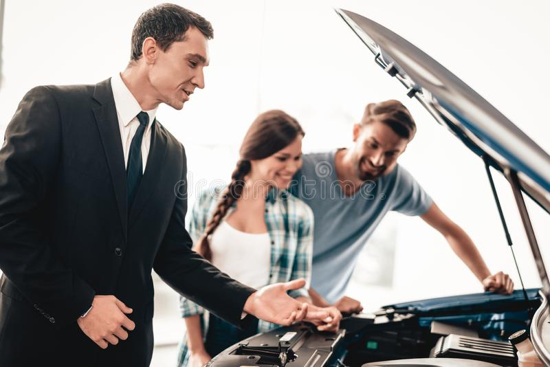 Young Family Are Choosing A New Car In Showroom. Happy Young Family Are Choosing A New Car In Showroom. Dialogue With Dealer. Cheerful Customer. Automobile stock images