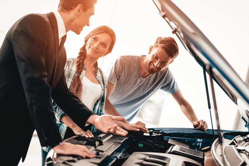 Young Family Are Choosing A New Car In Showroom. Happy Young Family Are Choosing A New Car In Showroom. Dialogue With Dealer. Cheerful Customer. Automobile stock photos
