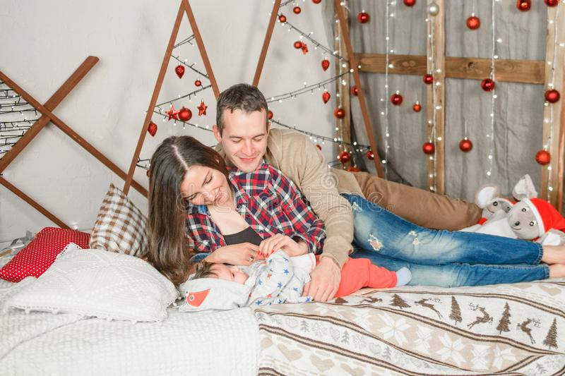 Young family at christmas. celebrate the new year with your loved ones. happy family mom dad and child with a magic gift near the stock photography