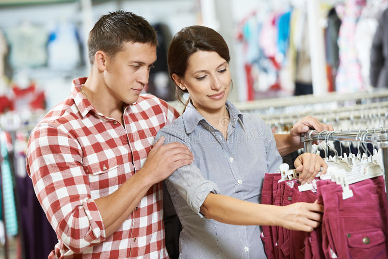 Young family at clothes shopping store. Young men and women family choosing outerwear during clothing shopping at supermarket store royalty free stock image