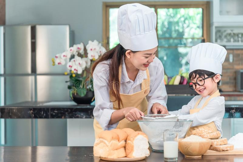 Young family cooking food in kitchen. Happy young girl with her mother mixing batter in the bowl royalty free stock photos