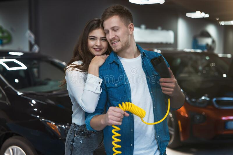 Young family couple beautiful brunette woman stands behind handsome man holding charging cable for electric car , looking happy royalty free stock images