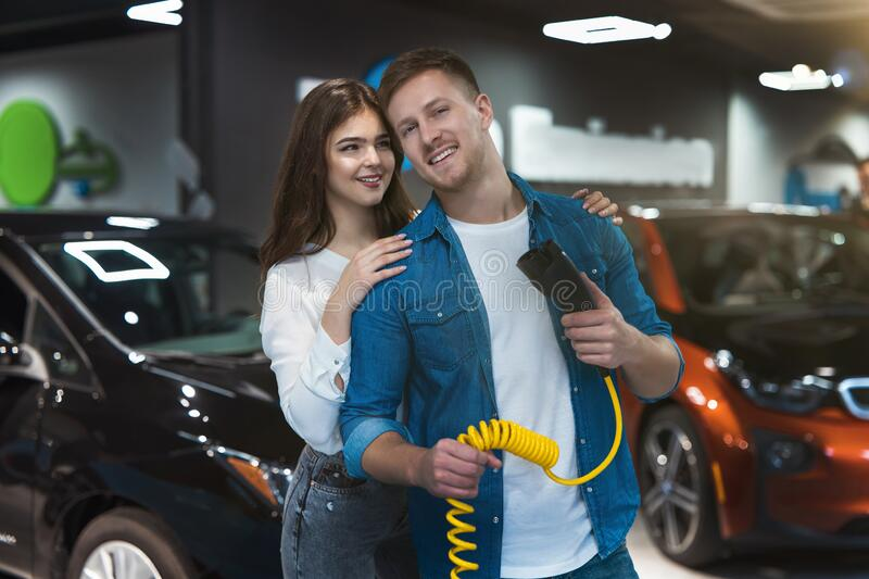 Young family couple beautiful brunette woman stands behind handsome smiling man holding charging cable for electric car , looking royalty free stock image