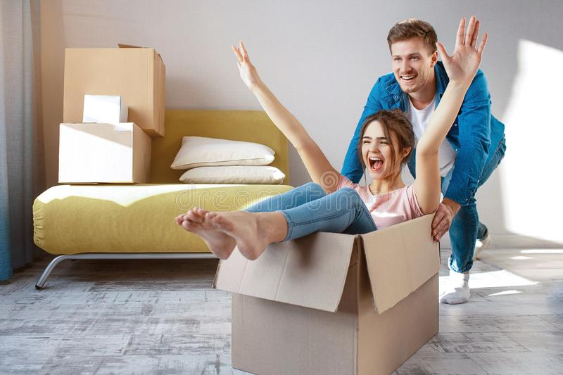 Young family couple bought or rented their first small apartment. Cheerful happy people having fun. She sit in box and royalty free stock images