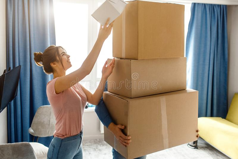 Young family couple bought or rented their first small apartment. Guy hold three cardboards. Young woman look up and royalty free stock photo